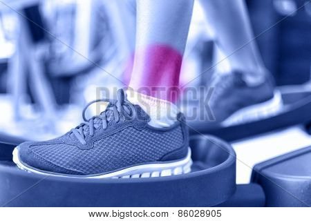 Hurting ankles - pain caused by fitness injury. Closeup of leg with red circle showing painful area of female athlete training on elliptical exercise machine. Sprained ankle concept.