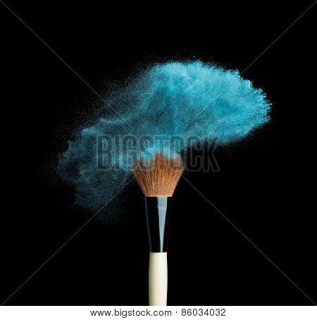 Isolated blue make-up powder with brush on black background