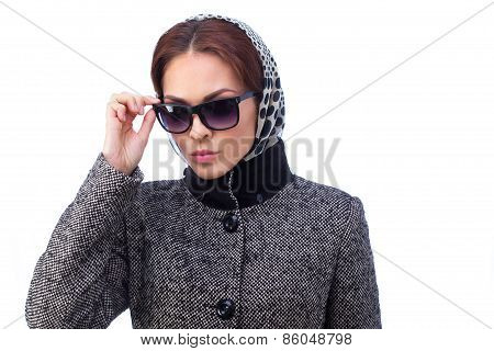 Fashion young woman is wearing sunglasses and coat. All isolated on white background.