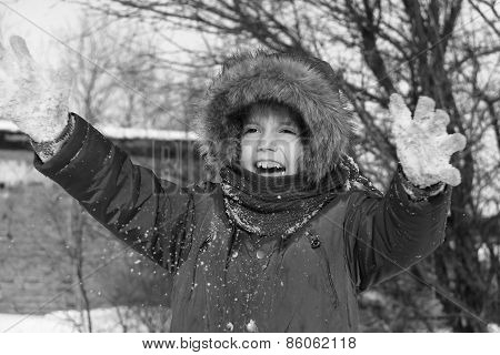 Preschool Girl Is Playing With Snow Outside In A Winter Day