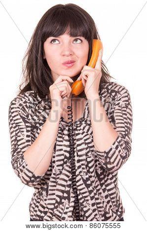 beautiful young woman using retro orange telephone