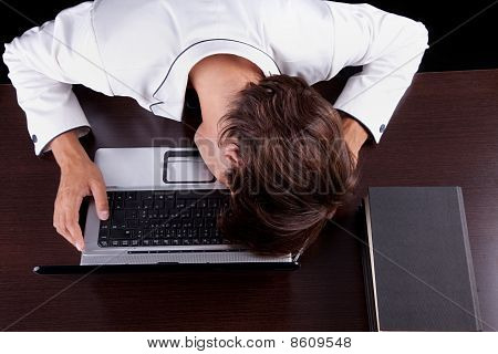 Tired Young Businessman With Head On The Computer On A Black Background. Studio Shot