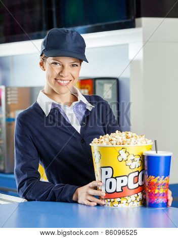 Portrait of smiling female worker with popcorn and drink at concession stand in cinema