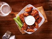 bbq buffalo chicken wings with beer ranch and celery shot top down poster