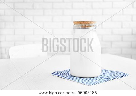 Glass jar of milk on wooden table, on bricks wall background