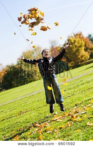little boy throwing up  leafes in the park