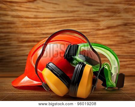 Red safety helmet with earphones and goggles poster