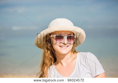Bright portrait of attractive young woman in sunglasses on the beach having sunbath