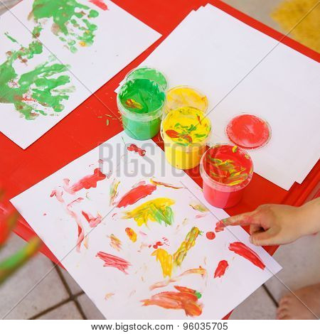 Child Painting A Drawing With Finger Paints