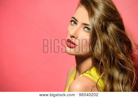 Fashion model in bright yellow dress posing over pink background. Beauty, fashion concept. Hair, healthy hair.