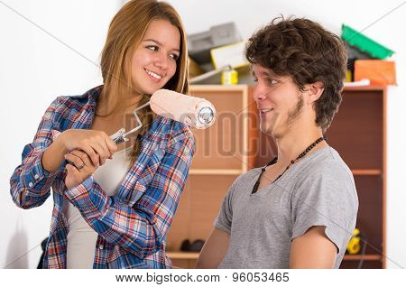 Couple renovating together as she holds up a roller with pink paint in front of his face