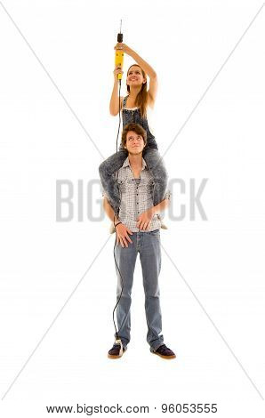 Couple wearing denim working with renovation as woman sitting on mans shoulders and holding up a pow