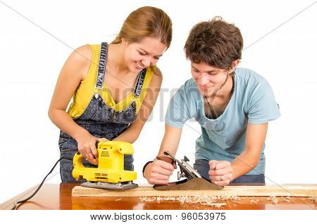 Couple standing by working desk as woman uses electric sander and man holding a manual version