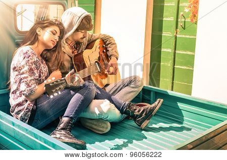 Romantic Young Couple Of Lovers Playing Guitar Outdoor With Sunshines After The Rain