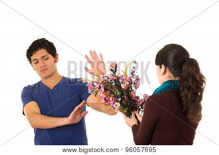 Hispanic couple fighting as man refuses to receive flowers from woman