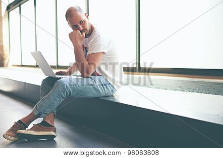 Young man looking thoughtful while working on laptop computer holding it on the knees