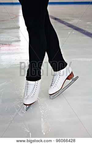 Woman's Legs In White Ice Skates