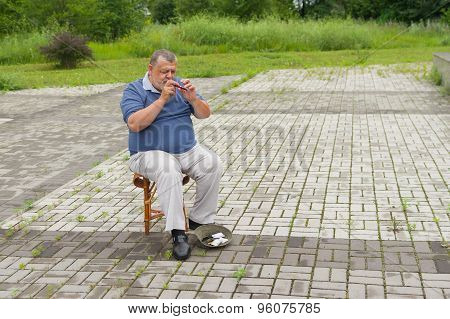 Lonely musician on a street playing  woodwind instrument sopilka