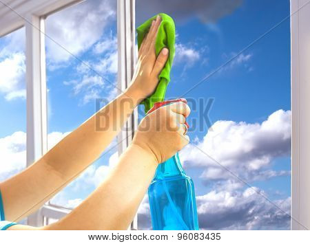 Person is cleaning a window with spray