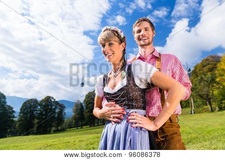 Couple in Tracht standing on meadow in alp mountains, a cable car is running in the background