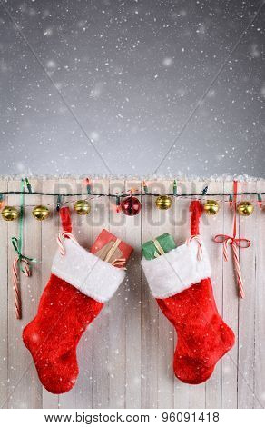 Two Christmas Stockings hanging on a rustic white fence with lights, jingle bells, and candy canes. Vertical format with snow effect.