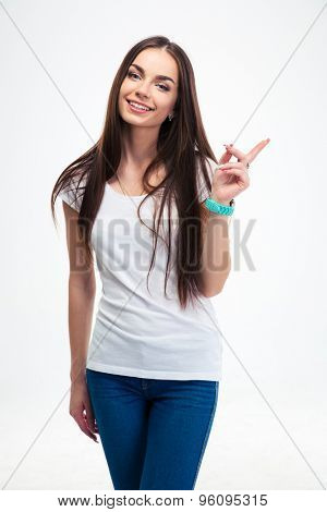 Smiling beautiful woman pointing finger away isolated on a white background