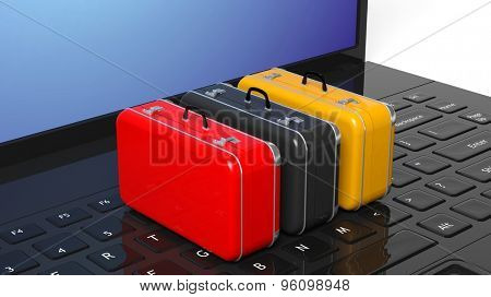 Colorful suitcases on black laptop keyboard with blank screen