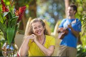 Grinning adult female listening to musician in Hawaii poster