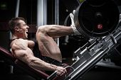 Man in gym training at leg press to define his upper leg muscles poster