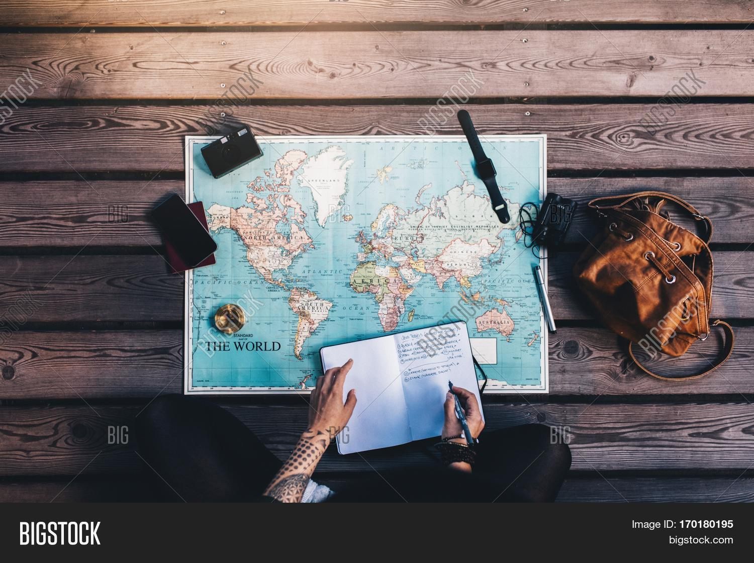 Imagen y foto young woman making prueba gratis bigstock young woman making notes in diary looking at the world map with travel accessories around gumiabroncs Image collections