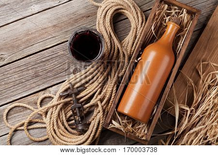 Red wine bottle in box and glass on wooden table. Top view with copyspace