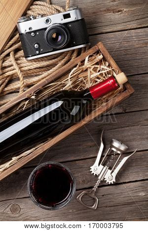 Red wine bottle in box and glass on wooden table. Top view