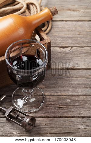 Red wine bottle and glass on wooden table