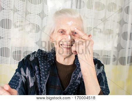 Cheerful Grandma Applying Face Cream