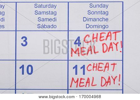 Close-up Of Cheat Meal Day Text Written On Calendar Date