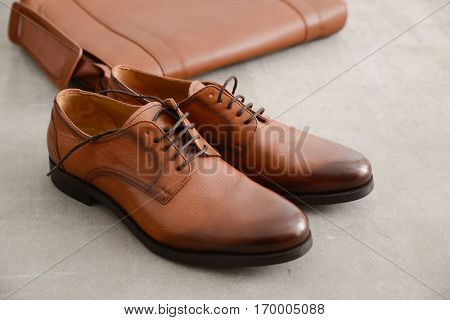 Men's casual outfits with brown shoes and brown handbag on gray grunge background
