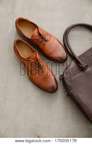 Men's casual outfits with brown shoes and handbag on gray background