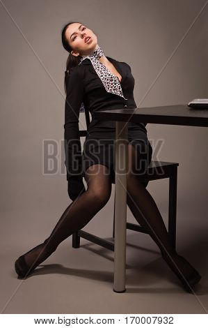 Woman In A Black Suit Sitting On A Office Table