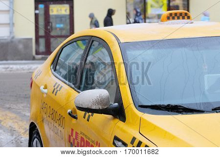 Moscow, Russia, December, 8, 2016: Close up image of snow-covered Moscow yellow taxi