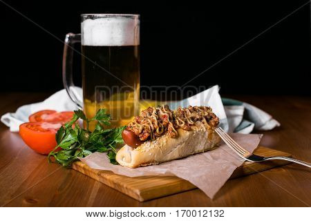 Hotdogs with the glass of beer with sweet bubbles in it. Hotdogs and chips on wooden table on dark background. Traditional American lunch.