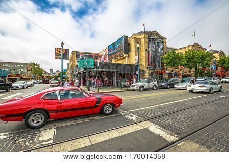 San Francisco, California, United States - August 14, 2016: Red vintage speed car on Jefferson rd corner Mason st. during the Sunday speed cars street carnival along the Fisherman's Wharf waterfront.
