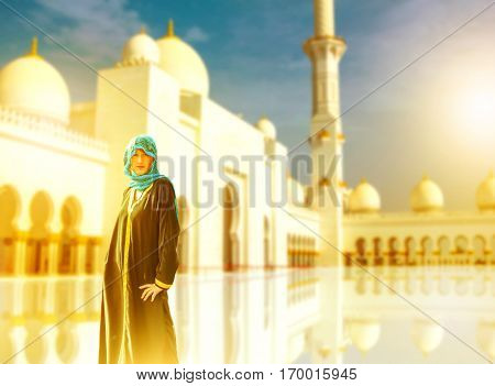 Woman with typical Arab clothes visit Sheikh Zayed Grand Mosque at sunset. Tourist visiting the main attraction of Abu Dhabi. Sheikh Zayed is the largest mosque in UAE. Middle East tourism concept.