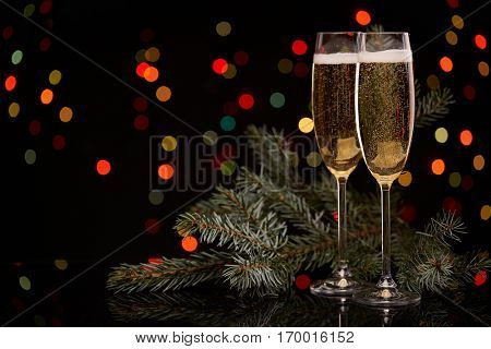 Two glasses with champange and fir tree branch on a black background with multi-colored lightes of garland.  New year and Christmas.