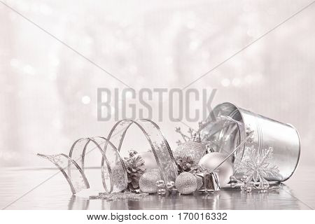 Christmas decoration with metal bucket, silvery pine cones, silvery balls and gift box lying on a silver background.  New year and Christmas background with copy space for text. Greeting card.