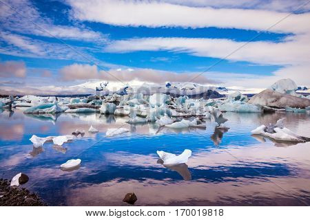 Clouds magically reflected in the smooth water of the lagoon. The concept of northern extreme tourism. The ice floes and cirrocumulus clouds of lagoon Jokulsarlon, Iceland