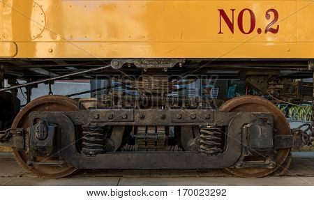 Section of Train Wheels underneath yellow car
