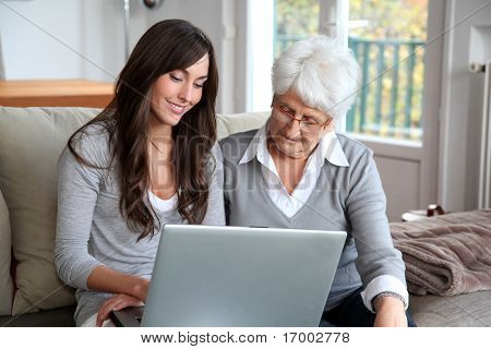 Young woman and elderly woman with laptop computer