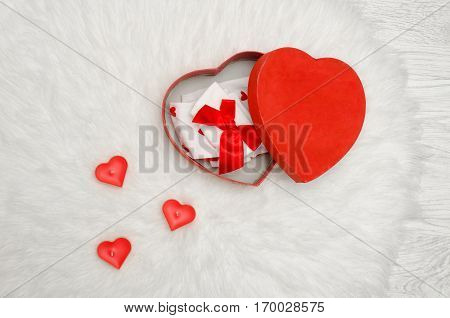 Open red box with heart shaped red and white linen on a white fur. Candles in the shape of a heart a top view