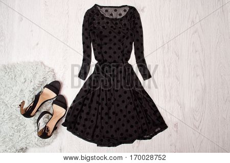 Black female dress with long sleeves and black shoes on a wooden background. Fashionable concept top view
