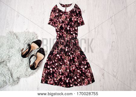 Black and pink dress with collar black shoes gray faux fur wooden background. Fashionable concept top view space for text